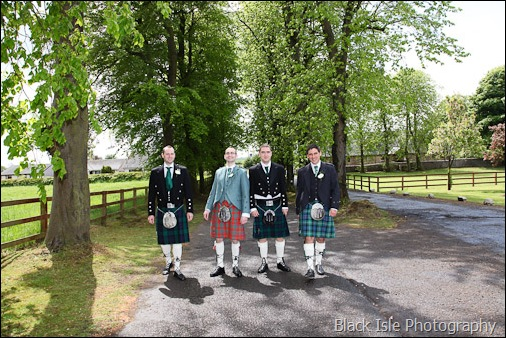 Aphotograph of the groom and his groomsmen at a highland wedding